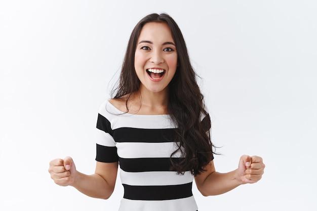 Luky, entusiasmada e bonita garota morena do leste asiático motivada, vitória determinada, punhos cerrados fortalecidos, sorrindo emocionado e alegre, sentindo-se animado assistindo a um jogo emocionante, fundo branco