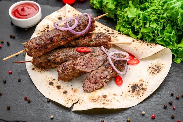 Lula kebab com batata, legumes e molho, em superfície preta