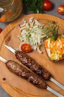 Lula kebab com cebola em conserva e salada de repolho