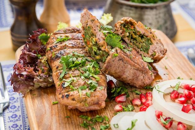 Lula kebab com ervas numa superfície de madeira