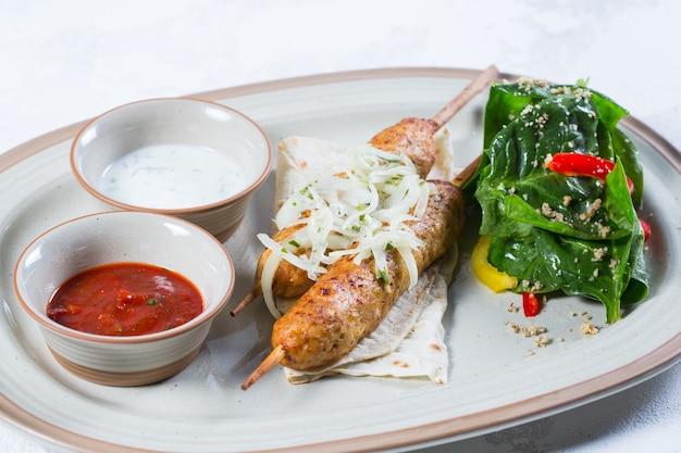 Lula-kebab de frango com cebola e molho vermelho picante.