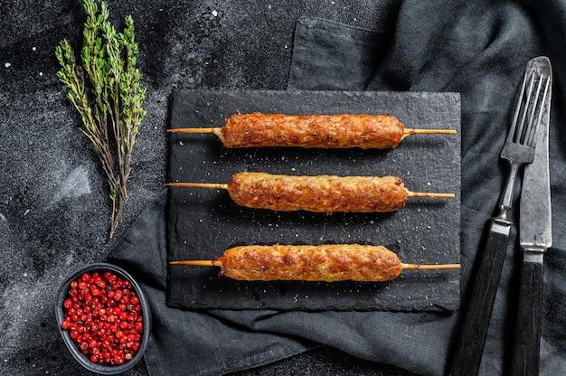 Lula kebab. shish kebab no palito, de carne moída. fundo preto.