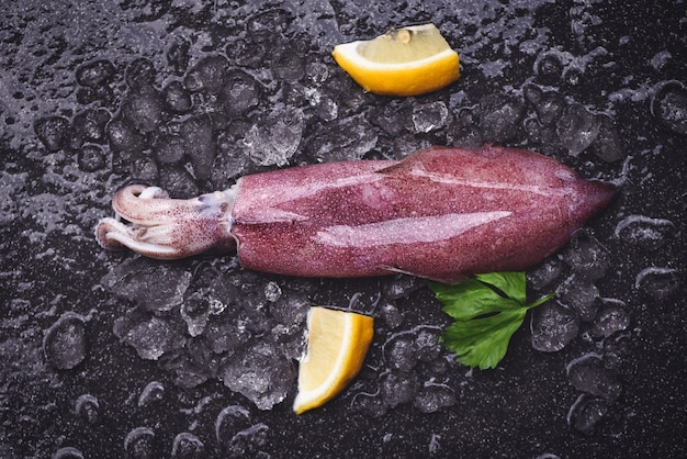 Lulas frescas de polvo ou choco para salada de comida cozida, lula crua no gelo com salsa de limão no mercado de frutos do mar da placa escura