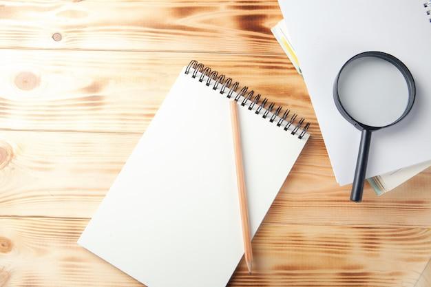 Lupa, caderno e caneta na mesa de madeira
