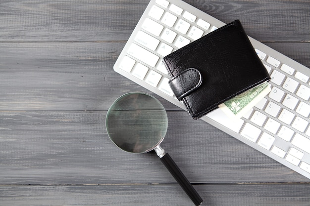 Lupa, carteira e teclado em uma mesa de madeira cinza. conceito de arrecadação de fundos online