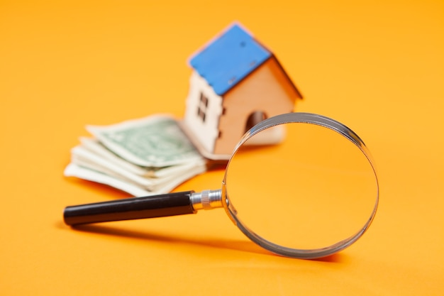 Lupa, casa e dinheiro em uma superfície amarela. conceito de estudo de custo de casa