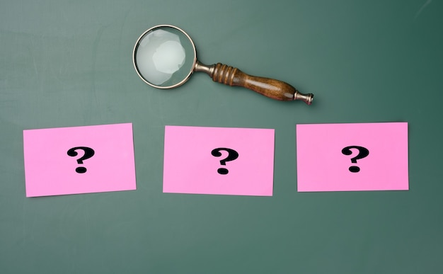 Lupa de madeira e pontos de interrogação desenhados de giz branco em uma placa de giz verde. o conceito de encontrar soluções, verdadeiras ou falsas. respostas em questões