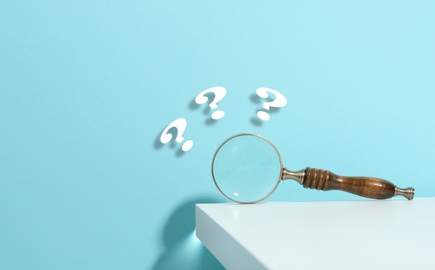 Lupa de madeira e pontos de interrogação sobre um fundo azul. o conceito de encontrar uma resposta para perguntas, verdade e incerteza.