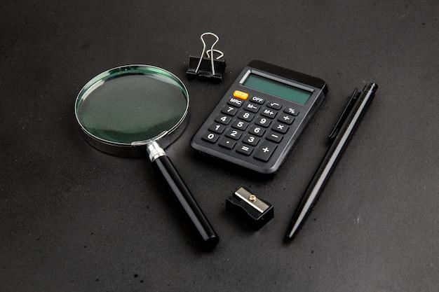 Lupa de vista inferior e clipe de pasta de calculadora apontador de caneta na parede escura