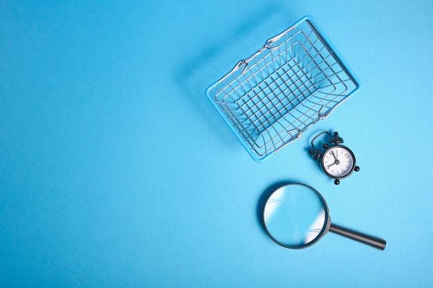 Lupa, despertador e carrinho de compras em miniatura no fundo azul, vista superior, copie o espaço