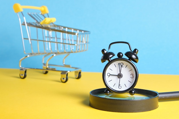 Lupa, despertador em carrinho de compras em miniatura no espaço de cópia de fundo amarelo e azul