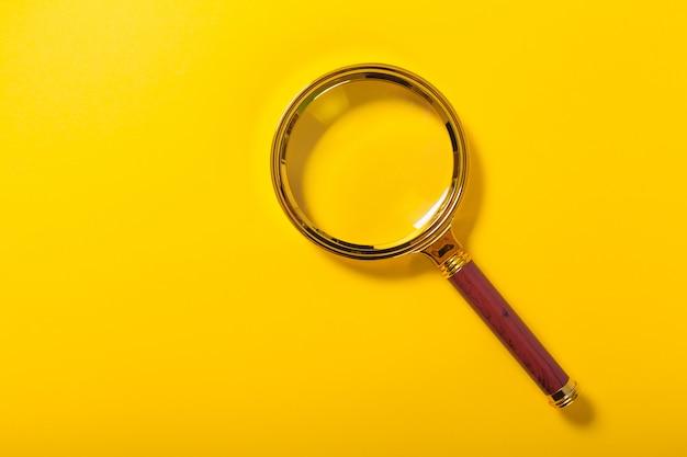 Lupa dourada sobre fundo de papel amarelo