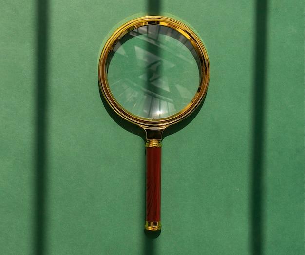 Lupa dourada sobre fundo verde com listras de sombra como conceito de encontrar respostas