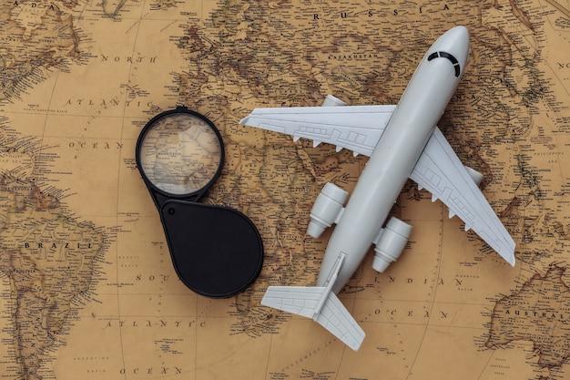 Lupa e avião no mapa antigo. viagem, conceito de aventura