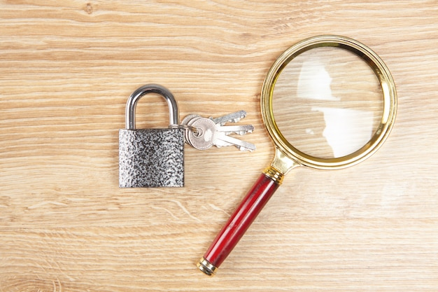 Lupa e bloqueio em uma mesa de madeira. conceito de busca de proteção