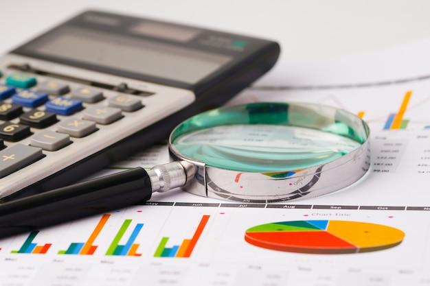 Lupa e calculadora em papel de gráficos.