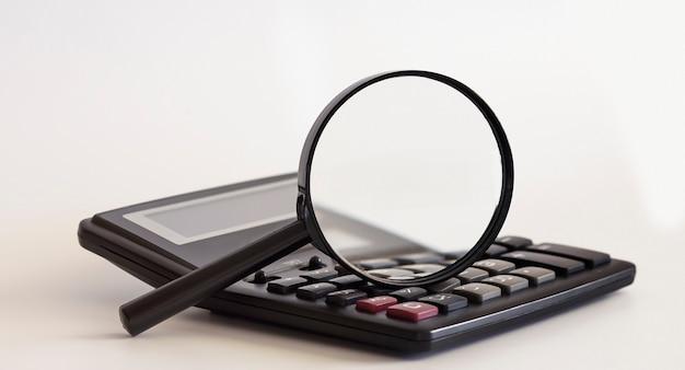 Lupa e calculadora na superfície branca
