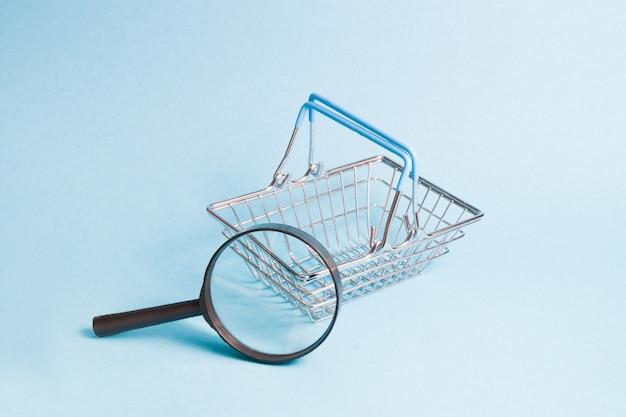 Lupa e carrinho de compras em miniatura
