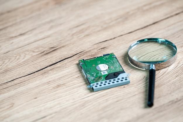 Lupa e computador de disco rígido em mesa de madeira para disco rígido de recuperação de dados