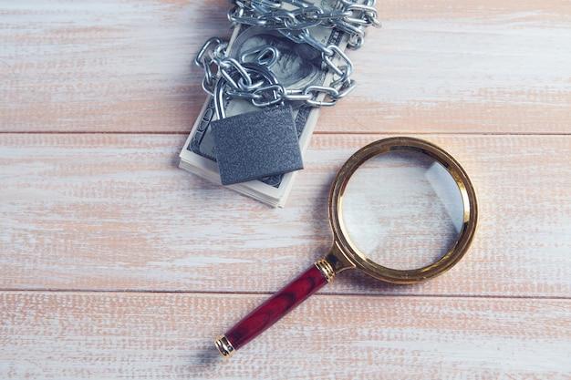 Lupa e dinheiro fechados com cadeado e correntes