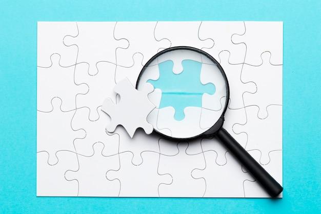 Lupa e falta de peça de quebra-cabeça no quebra-cabeça grade branca na superfície azul