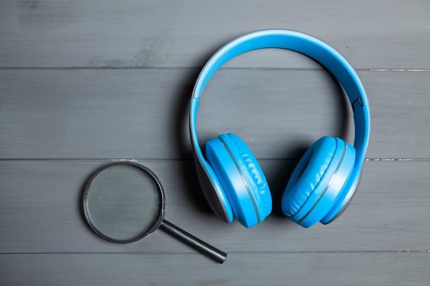Lupa e fones de ouvido na mesa de madeira cinza