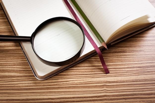 Lupa e livro sobre a superfície de madeira