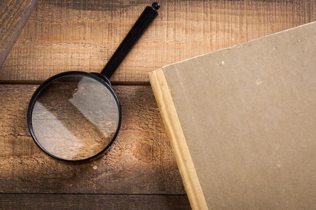 Lupa e livro sobre o fundo de madeira