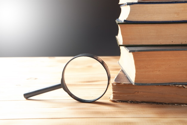 Lupa e livros sobre a mesa. conceito de estudo de livro