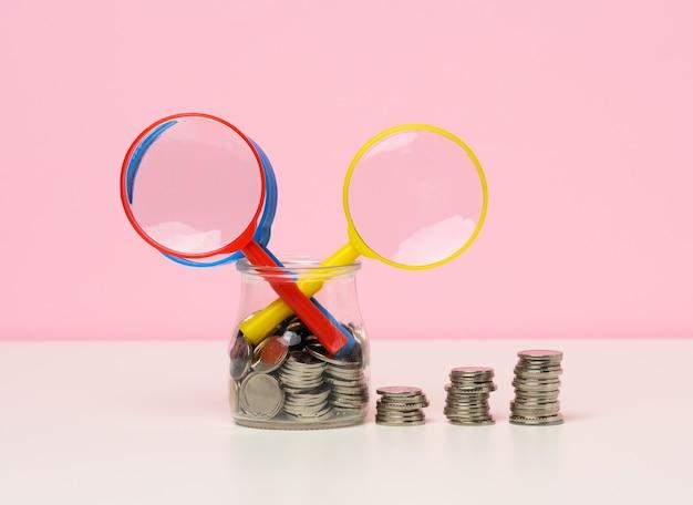Lupa e moedas brancas em cima da mesa. conceito de crescimento de renda, alta porcentagem de investimento. busca por novas fontes de renda, subsídio