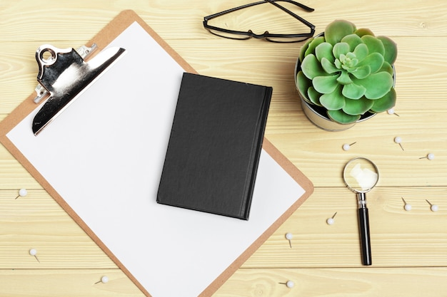 Lupa e notebook na mesa de madeira