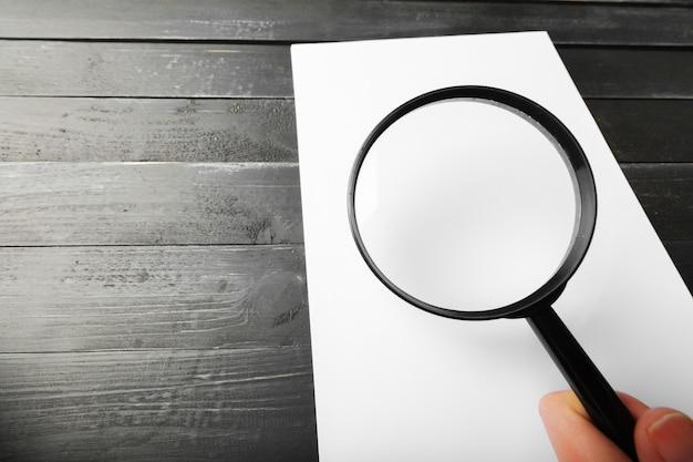 Lupa e papel em branco na mesa de madeira
