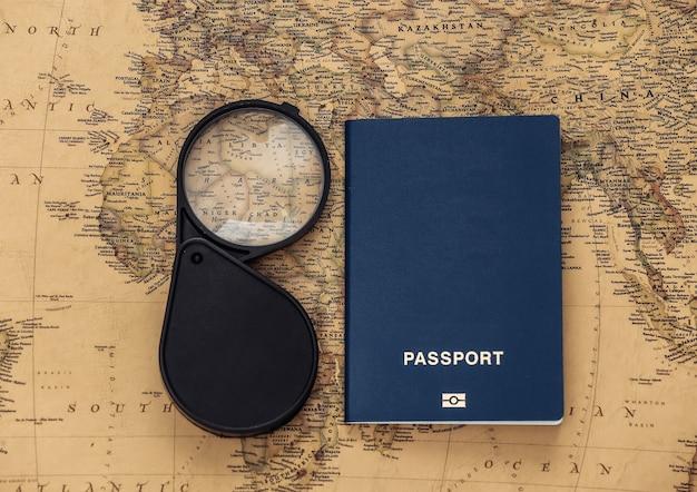 Lupa e passaporte no mapa antigo. viagem, conceito de aventura