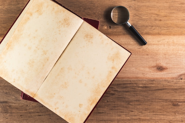 Lupa e pilha de livro antigo na mesa de madeira