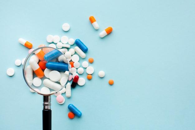 Lupa e pílulas coloridas