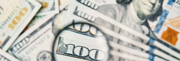 Lupa em fundo de contas de dólares. notas de cem dólares usd