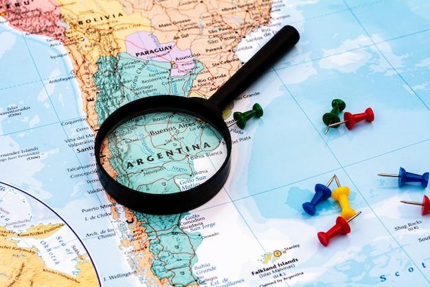 Lupa no foco seletivo de mapa do mundo em argentina. - conceito econômico e de negócios.