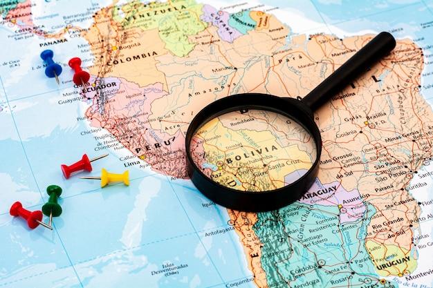 Lupa no foco seletivo de mapa do mundo no mapa de bolívia. - conceito econômico e de negócios.