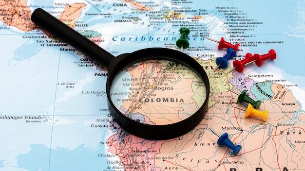 Lupa no foco seletivo de mapa do mundo no mapa de colômbia. conceito econômico e de negócios.