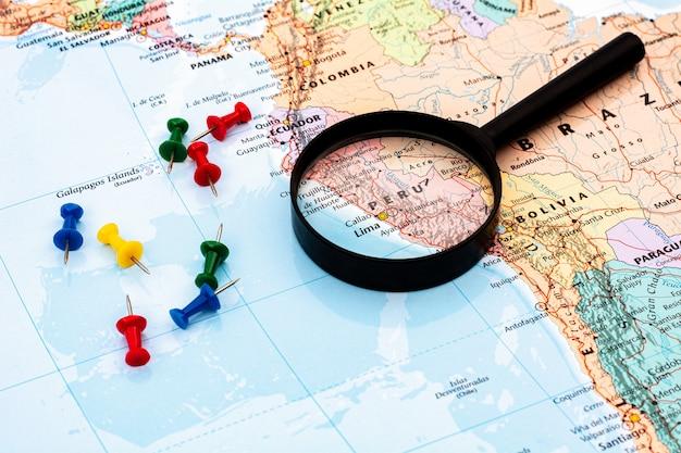 Lupa no foco seletivo do mapa do mundo em peru. econômico e comercial.