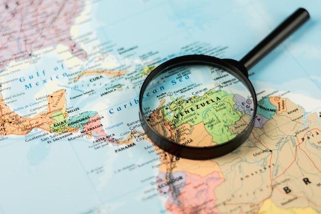 Lupa no foco seletivo do mapa do mundo em venezuela. - conceito de crise econômica.