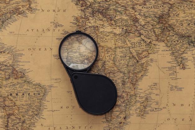 Lupa no mapa antigo. viagem, conceito de aventura
