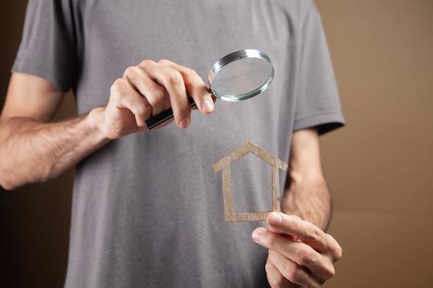 Lupa olha para a casa. pesquisa imobiliária em fundo marrom