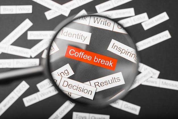 Lupa sobre a inscrição vermelha coffee-break recortada em papel.