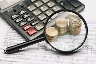 Lupa, sobre, a, moeda, pilha, e, calculadora, ligado, relatório financeiro