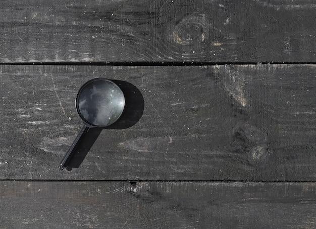 Lupa sobre fundo envelhecido em madeira com espaço de cópia para banner de madeira de texto com copyspace
