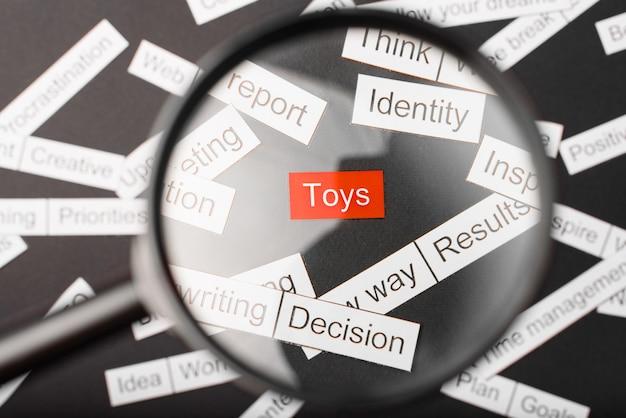 Lupa sobre os brinquedos com inscrição vermelha recortados em papel