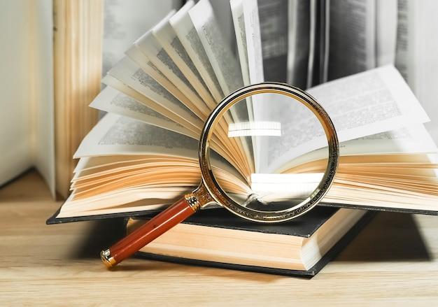 Lupas e livros com páginas viradas sobre a leitura da mesa de madeira e o conceito de conhecimento