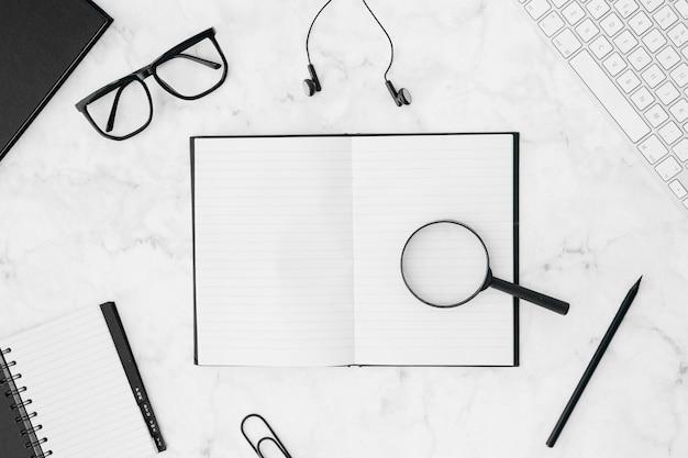 Lupas sobre o notebook rodeado de teclado; óculos; fone de ouvido; lápis; e diário no pano de fundo texturizado