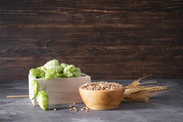 Lúpulo e ramos de trigo no espaço de madeira, lugar para texto.
